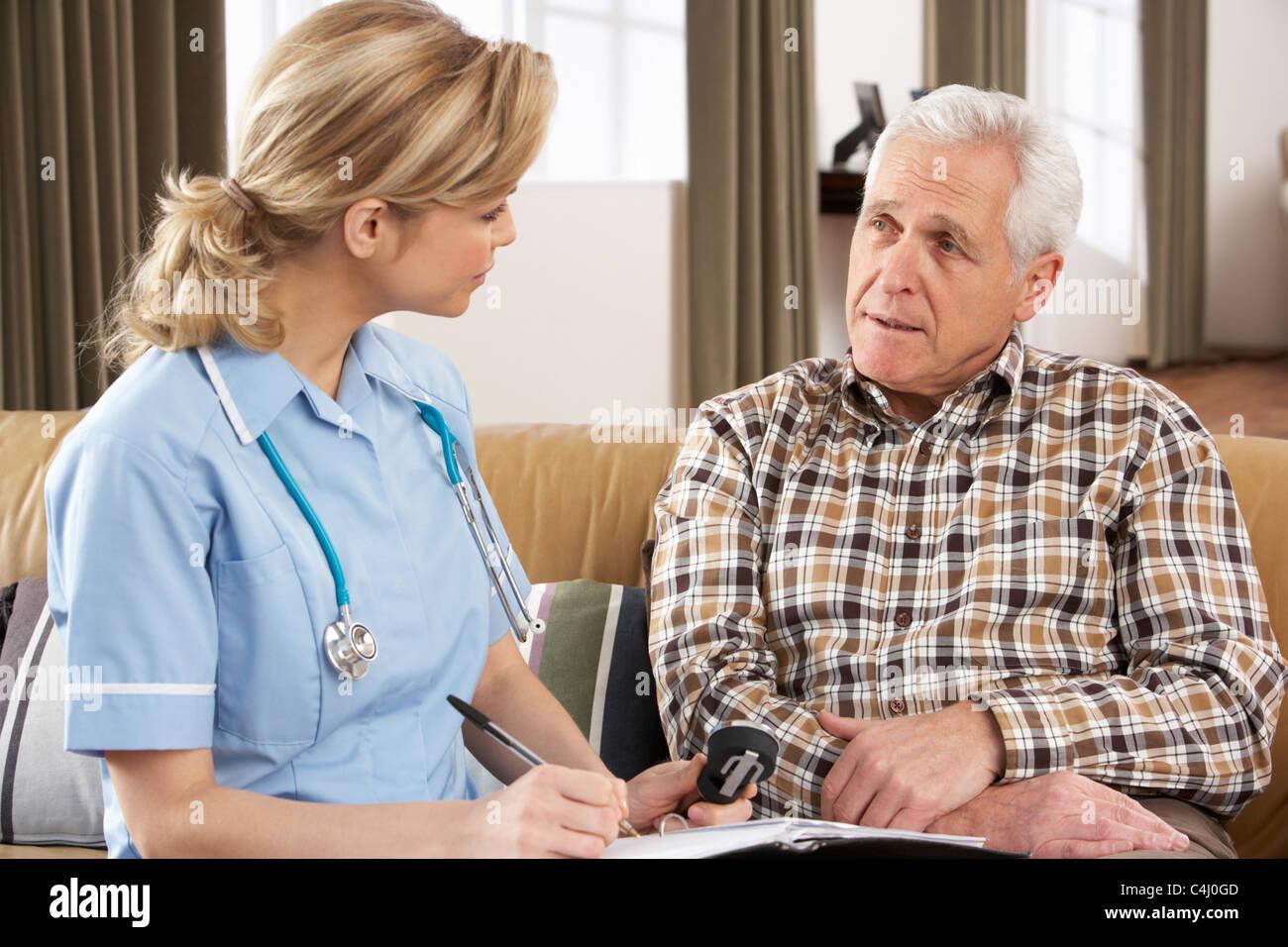 Senior Man Talking To Health Visitor At Home - Stock Image