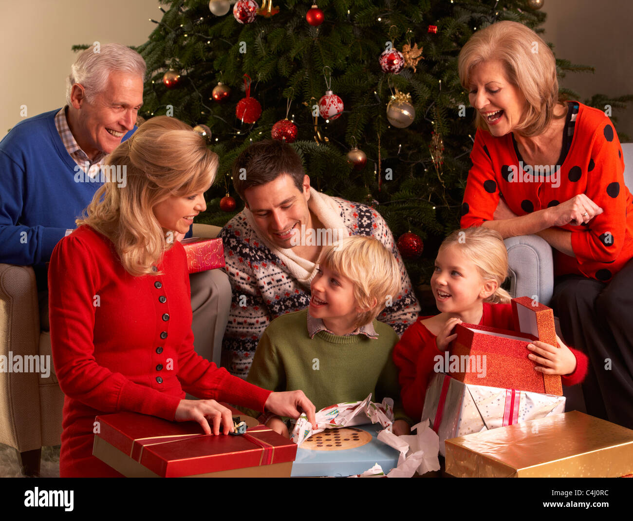 Three Generation Family Opening Christmas Gifts At Home Stock Photo ...