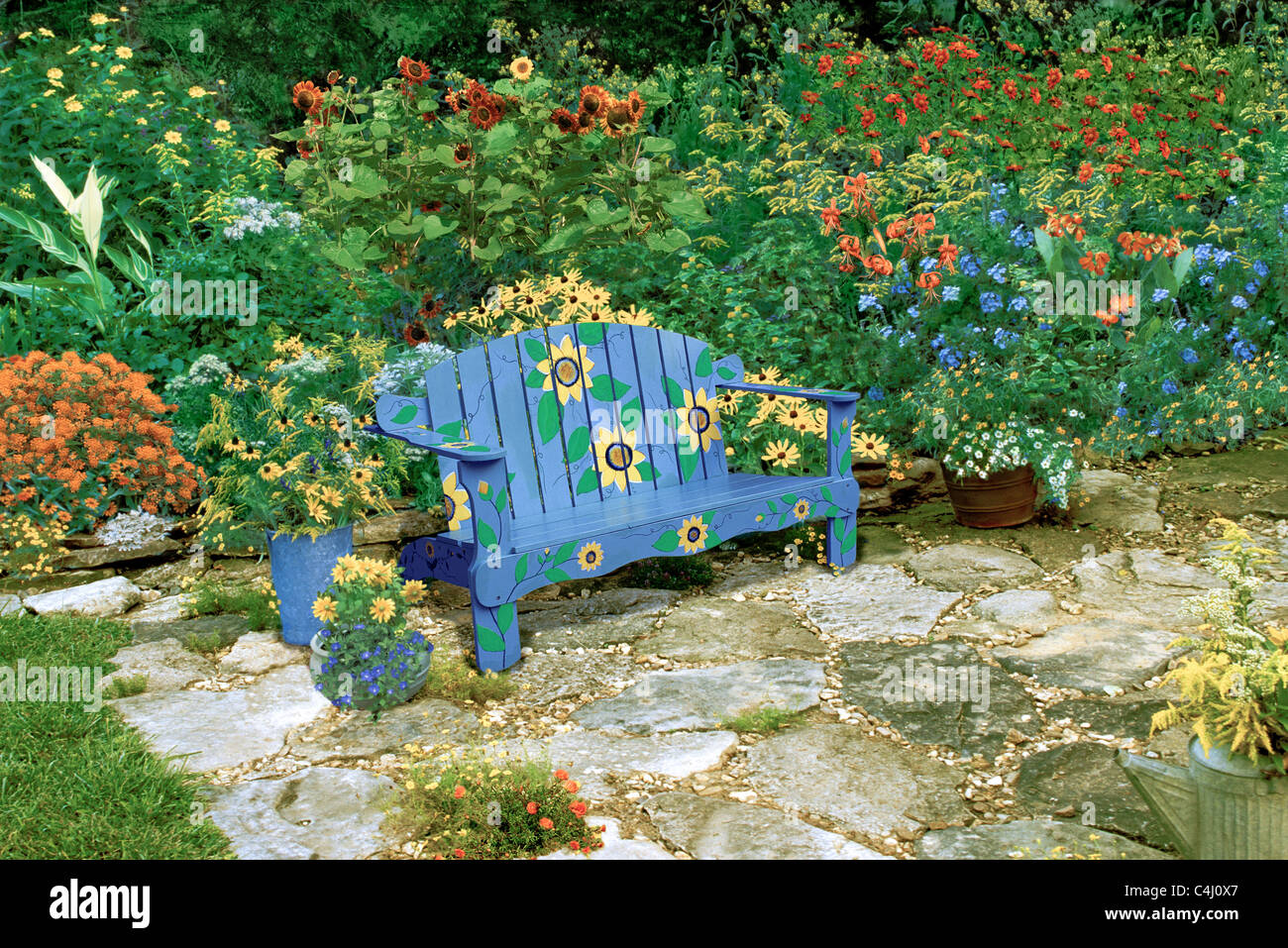 Blue Bench Painted With Sunflowers Sits In Garden Patio Of Stone Stock Photo Alamy