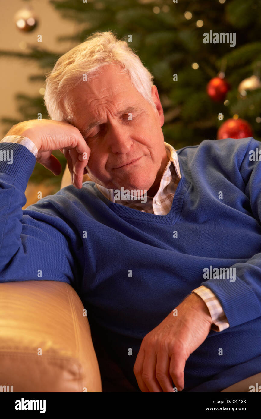 Tired Senior Man Relaxing In Front Of Christmas Tree Stock Photo