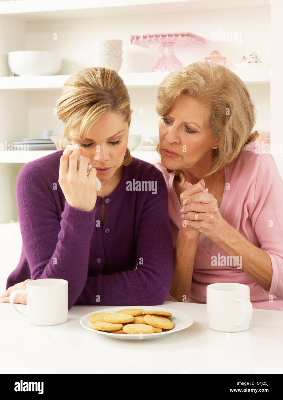 Mother Consoling Grown Up Daughter - Stock Image