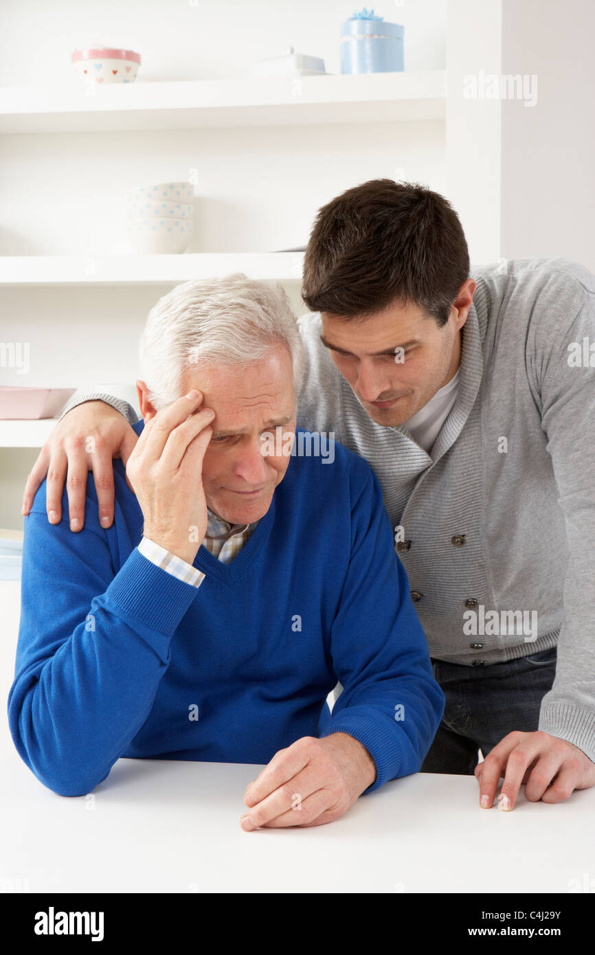 Grown Up Son Consoling Senior Parent - Stock Image