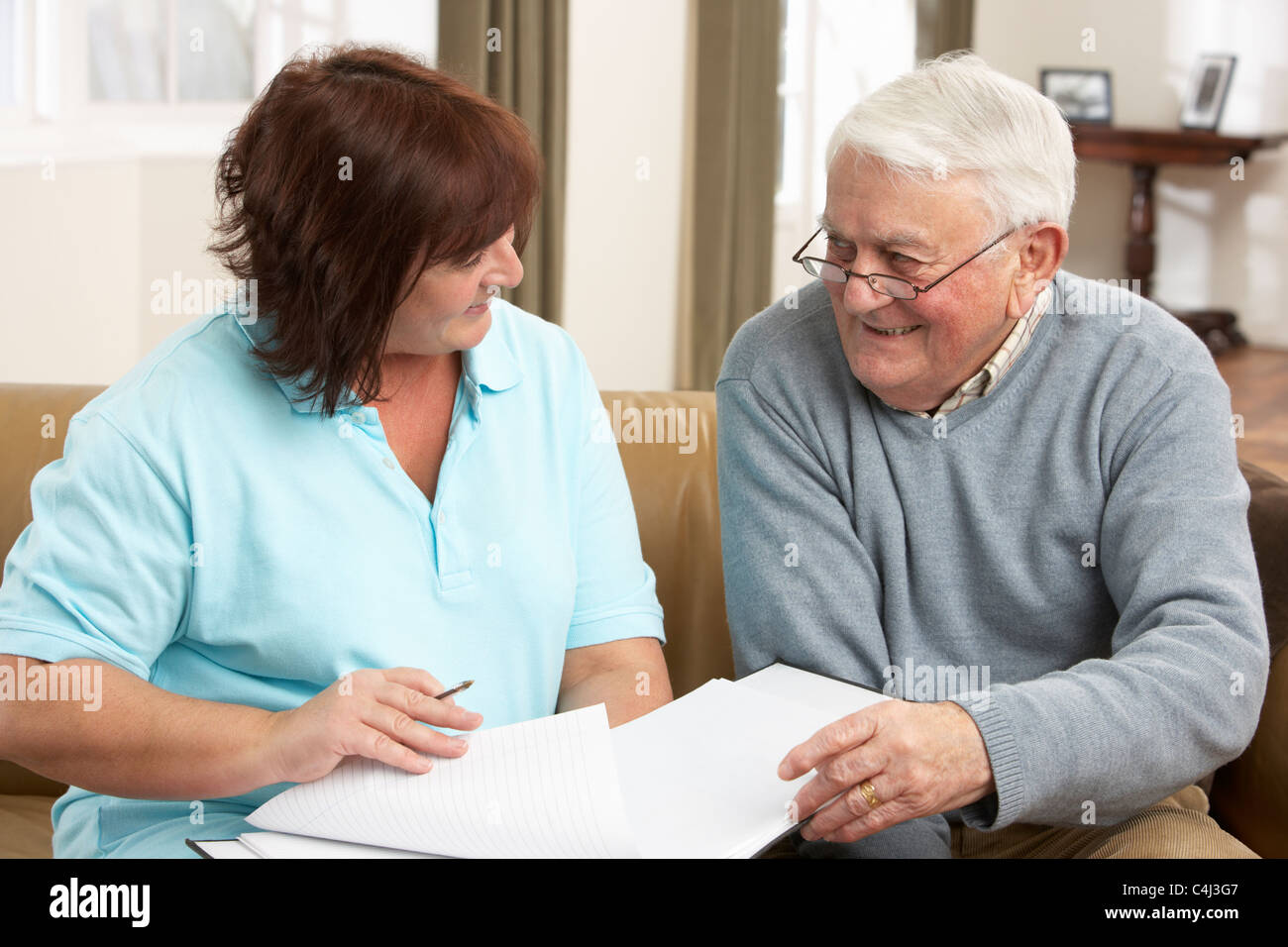Senior Man In Discussion With Health Visitor At Home - Stock Image
