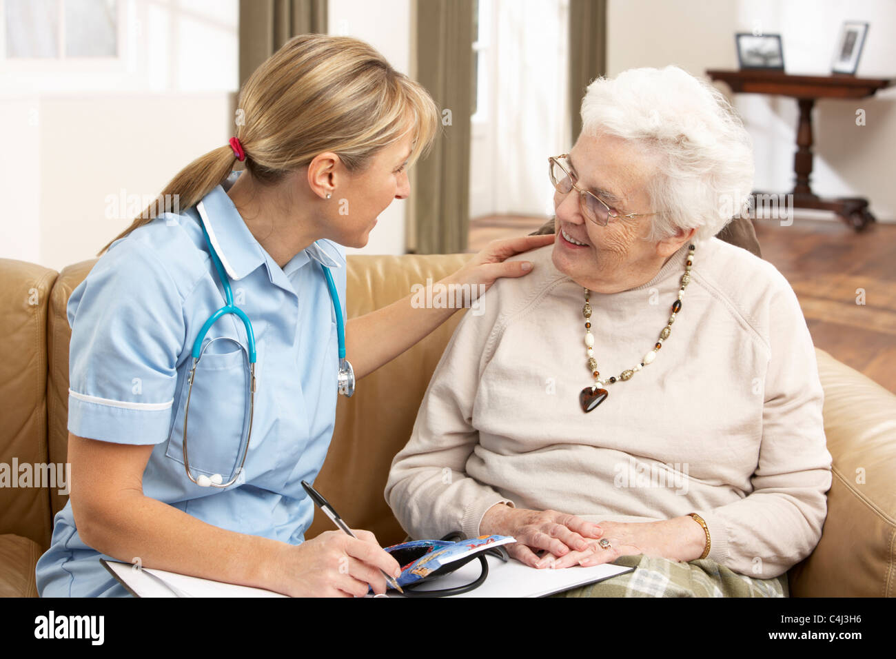 Senior Woman In Discussion With Health Visitor At Home - Stock Image