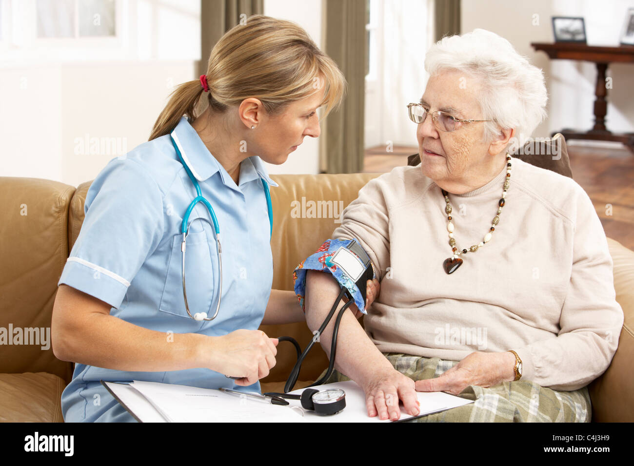 Senior Woman having Blood Pressure Taken By Health Visitor At Home - Stock Image
