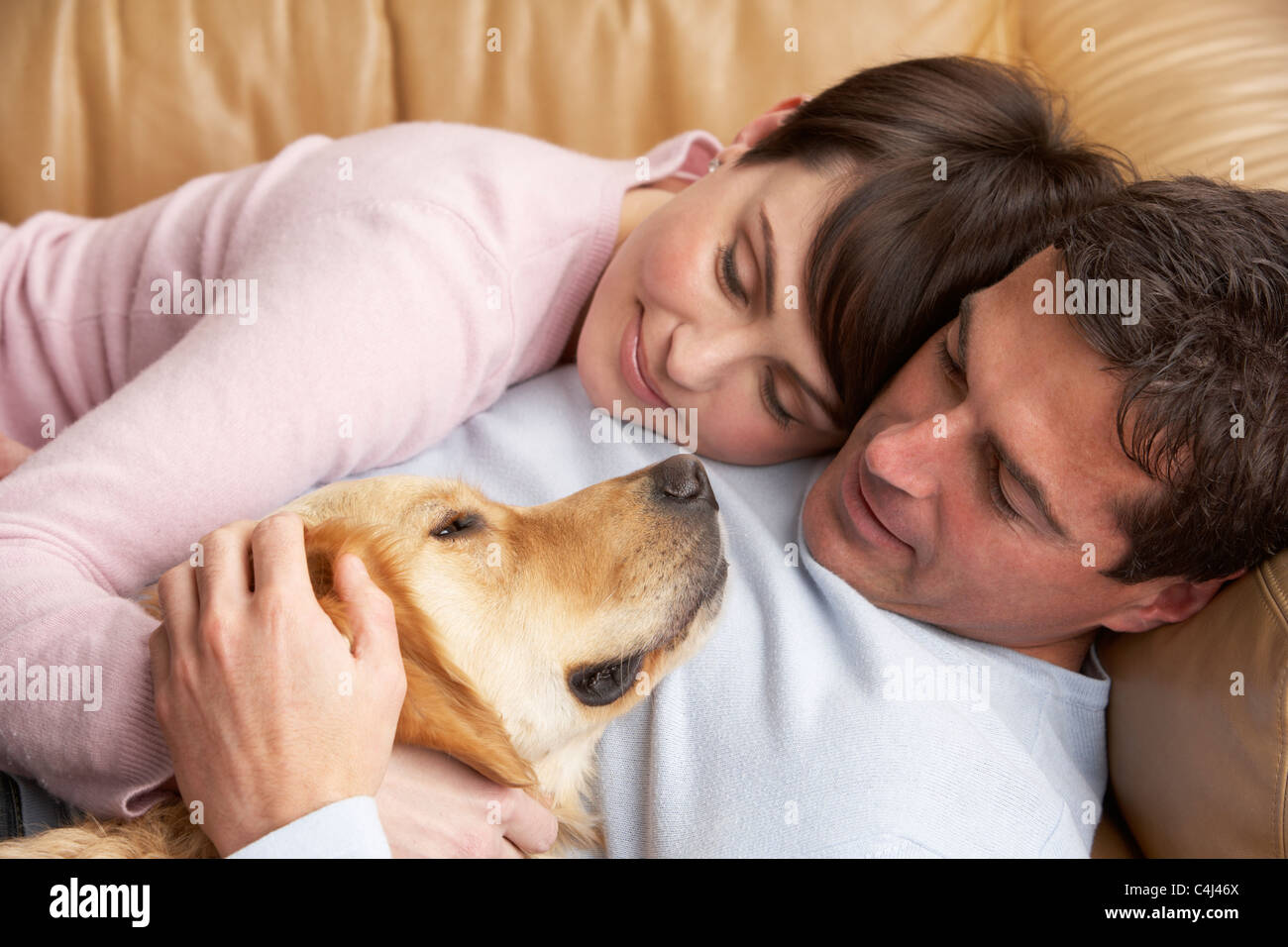 Portrait Of Couple Relaxing On Sofa With Pet Dog At Home - Stock Image
