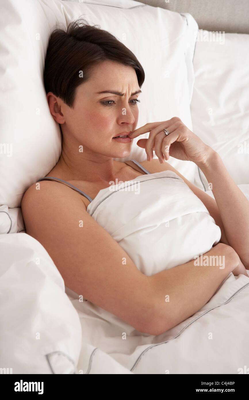 Worried Woman Laying Awake In Bed - Stock Image