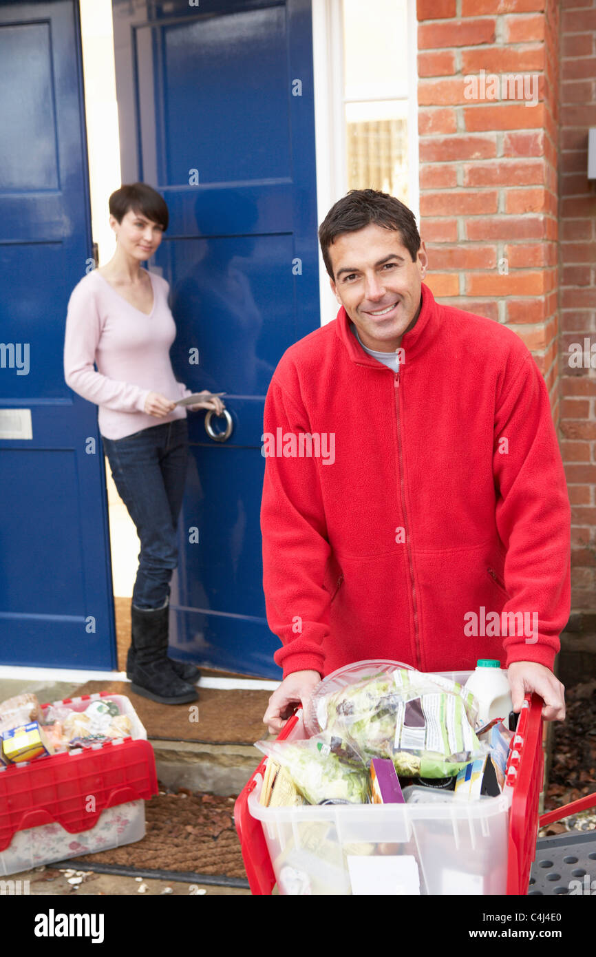 Home Delivery Grocery Driver Unloading Customer's Shopping - Stock Image