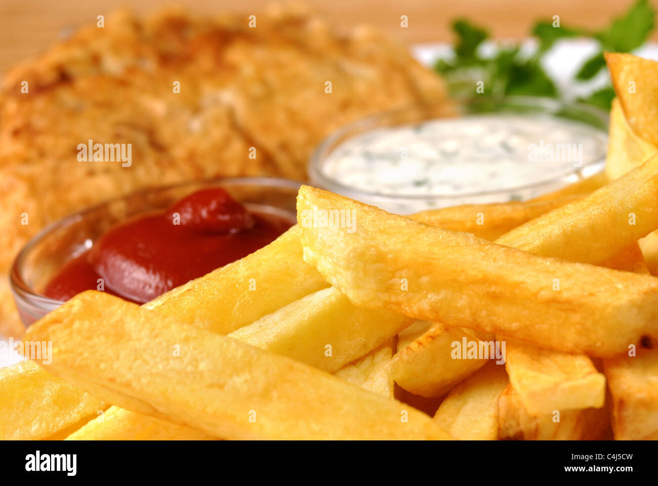 White plate with fish and chips, mayo and ketchup - Stock Image