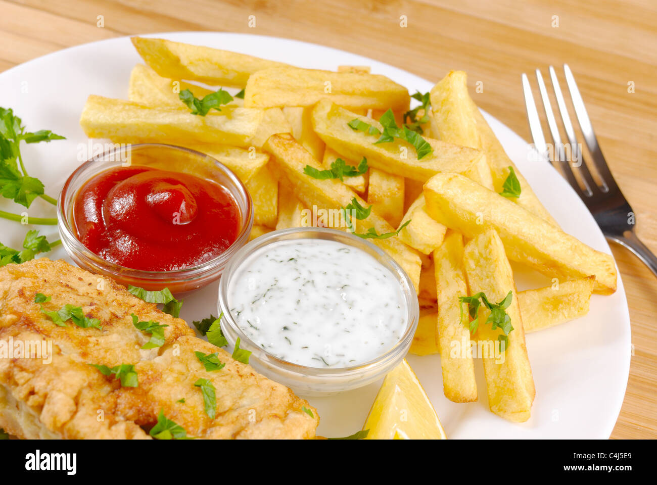 White plate with fish and chips, mayo, lemon and ketchup - Stock Image