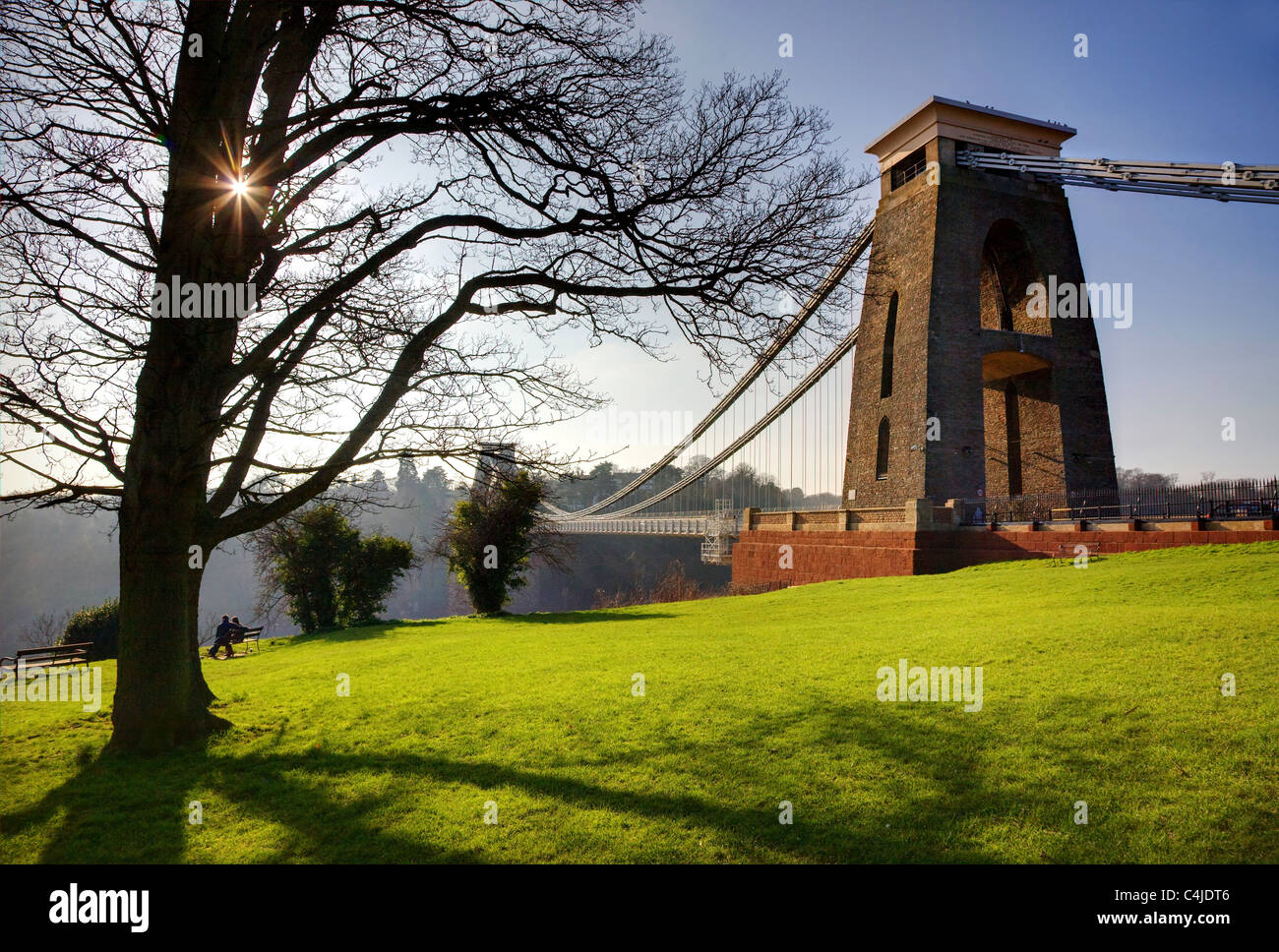 Clifton suspension bridge Bristol in early spring with sun peeping through trees and couple on a park bench Stock Photo