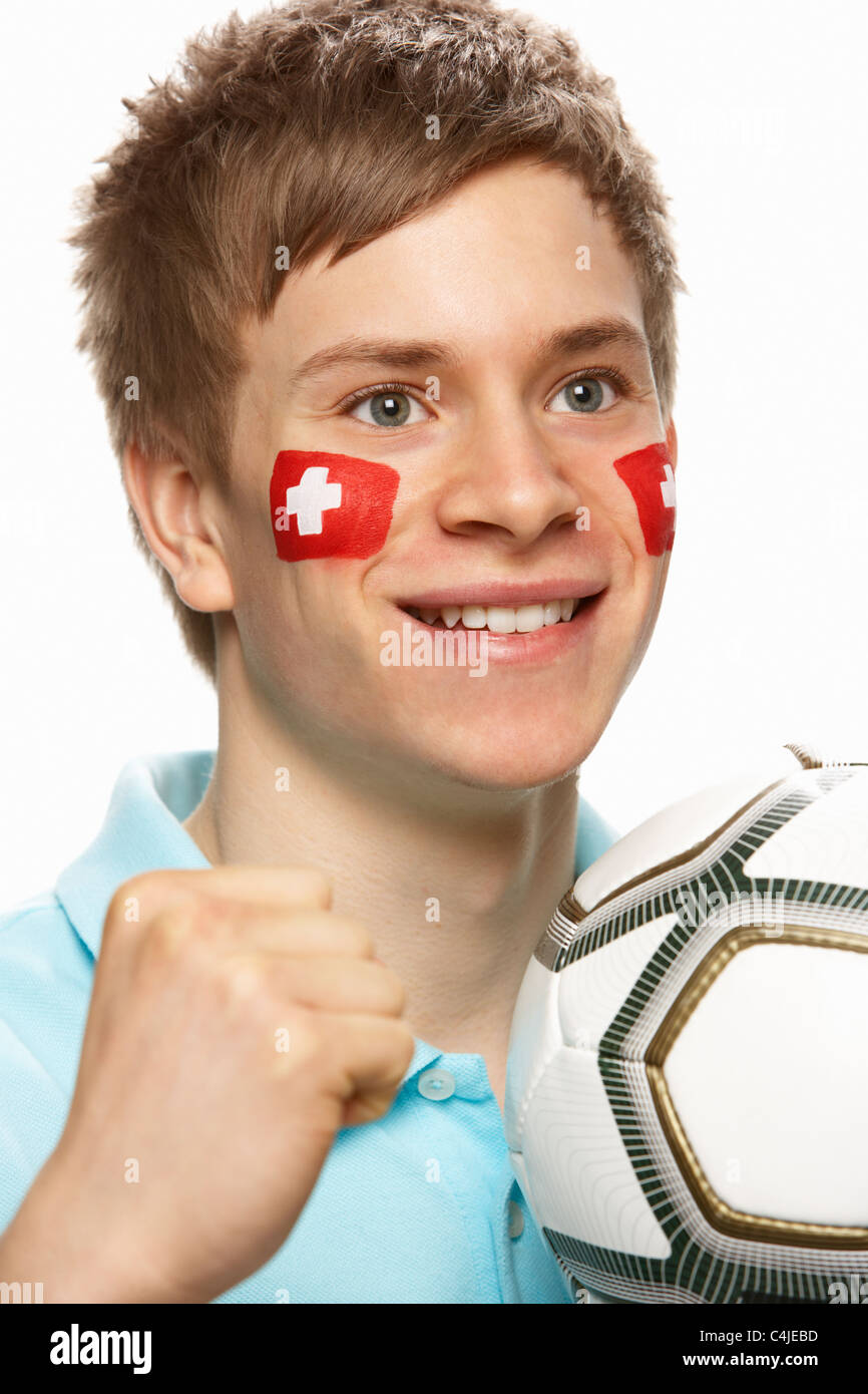Young Male Football Fan With Swiss Flag Painted On Face - Stock Image