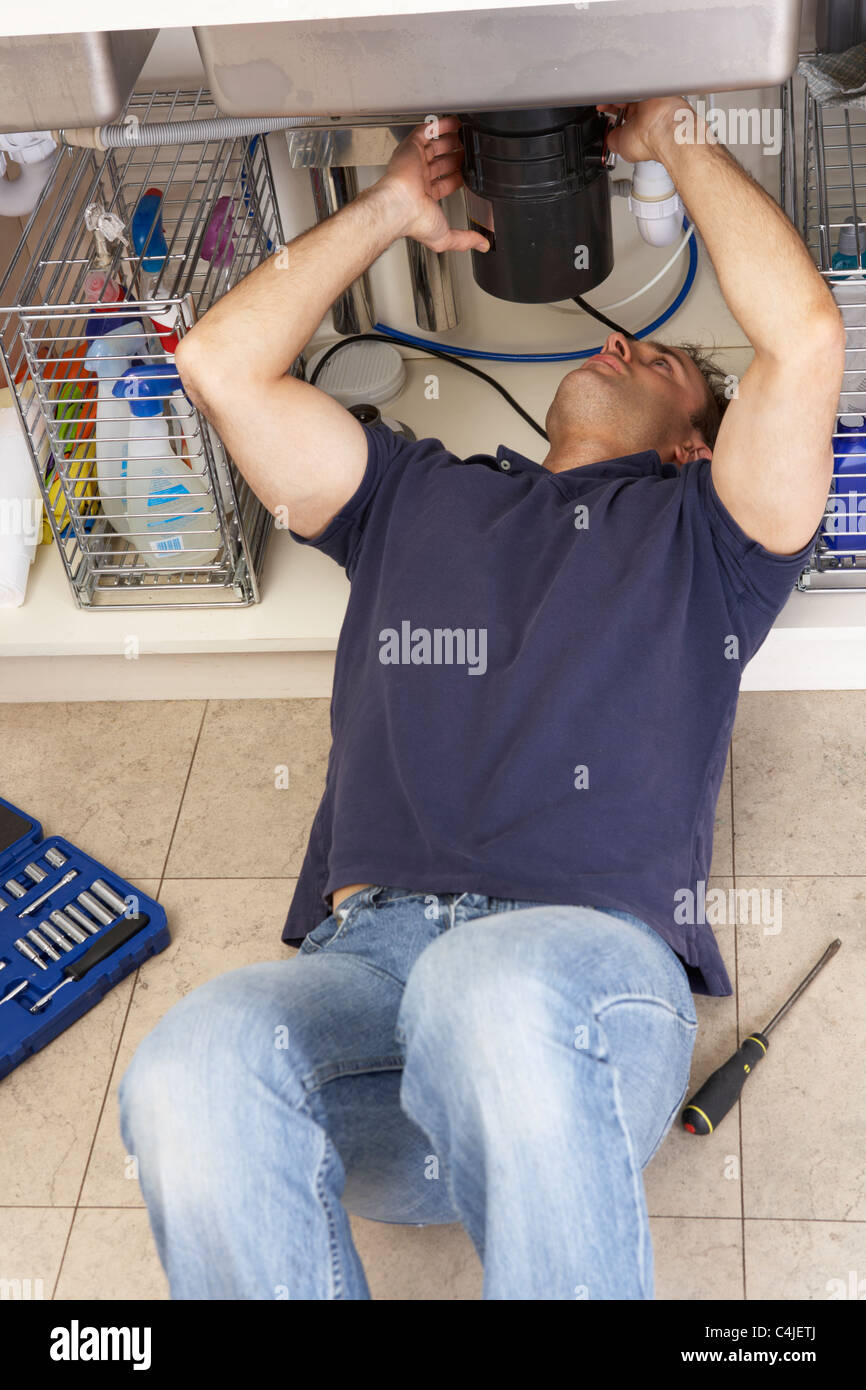 Plumber Working On Sink In Kitchen - Stock Image