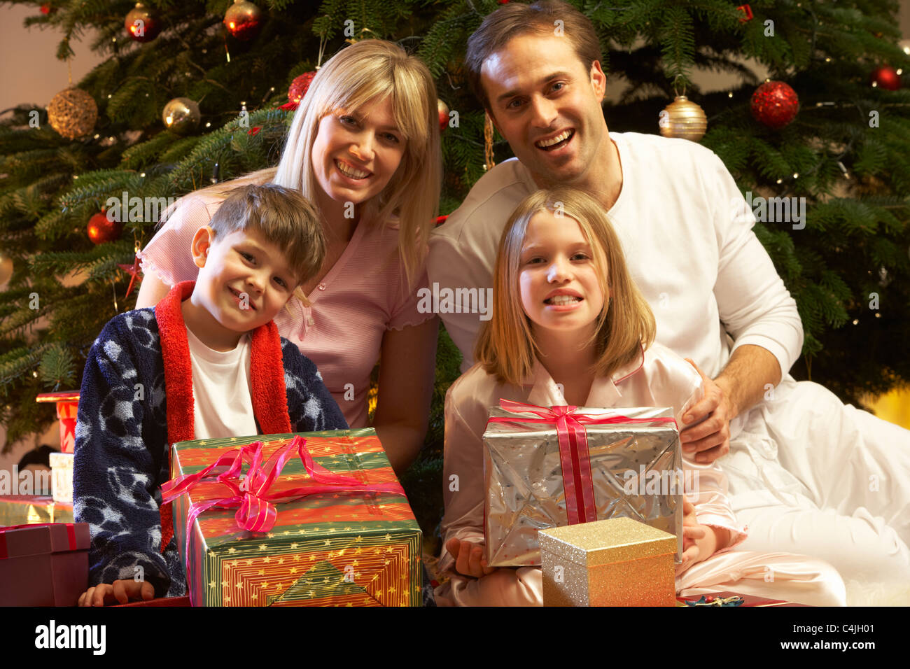 Family Opening Christmas Present In Front Of Tree Stock Photo