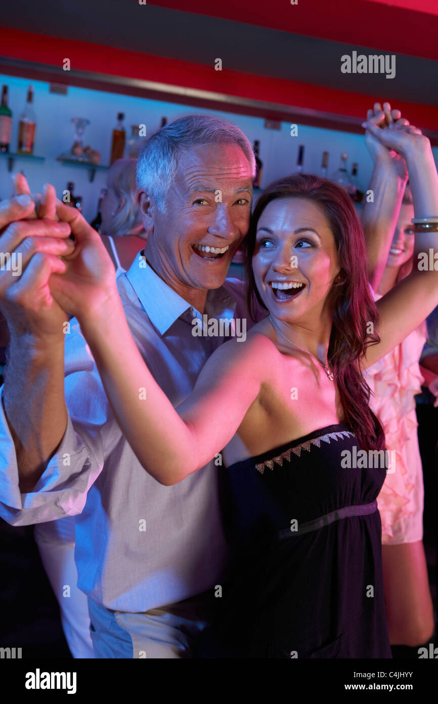 Senior Man Dancing With Younger Woman In Busy Bar - Stock Image