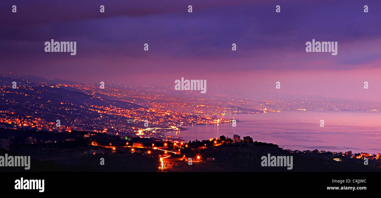 Panoramic mountains city at night with purple sky & sea - Stock Image