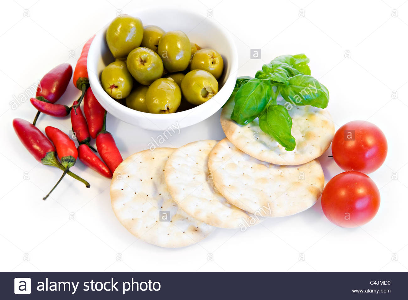 olives, hot chillies, cherry tomatoes and biscuits on white background - Stock Image