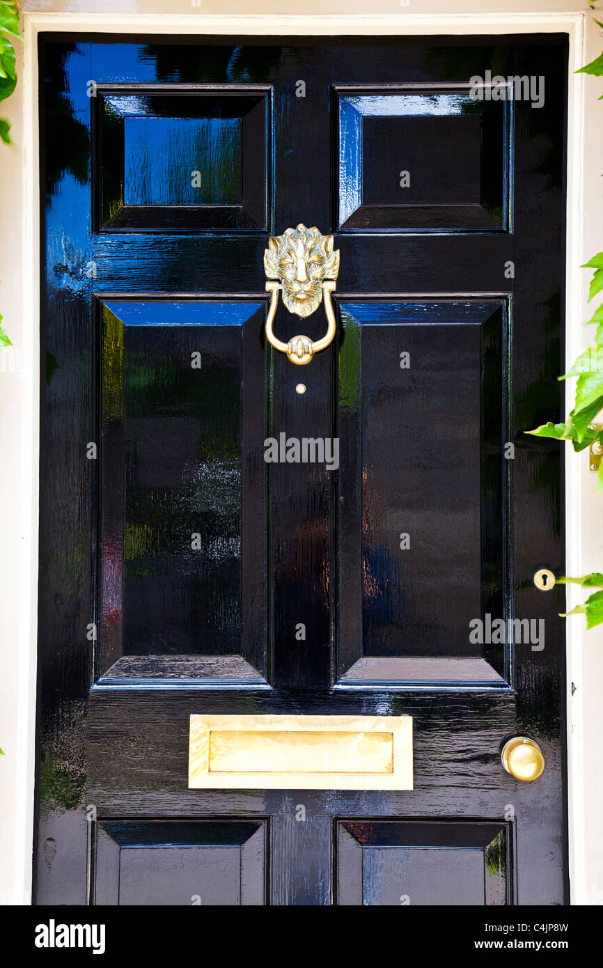 A shiny high gloss black painted front door with highly polished brass door furniture. - Stock Image