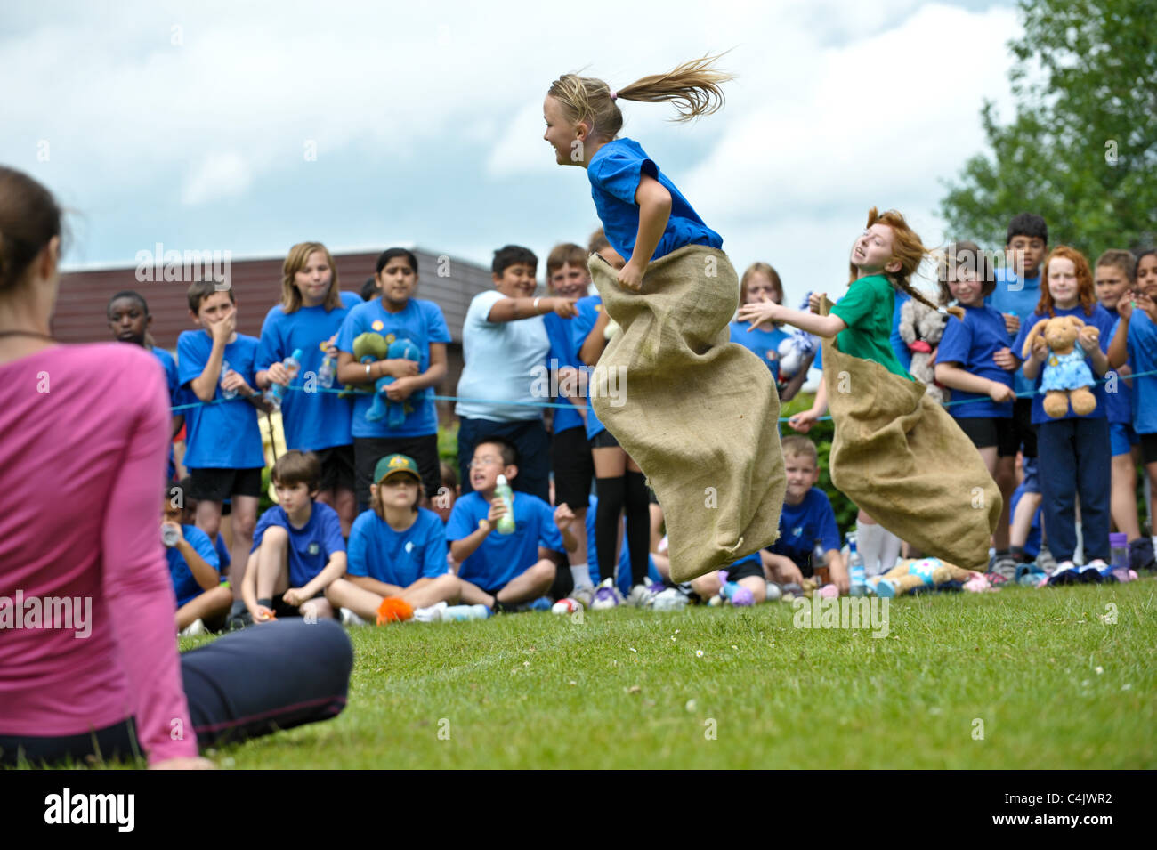 two school girls competing in a traditional school sports day sack race on the finishing line leaping up in the - Stock Image