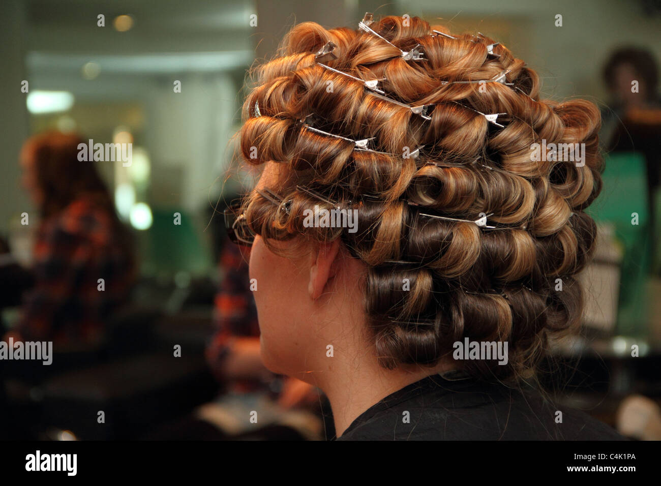 Hair in curlers at the hairdresser. A bride preparing for her big day. Beauty salon. - Stock Image