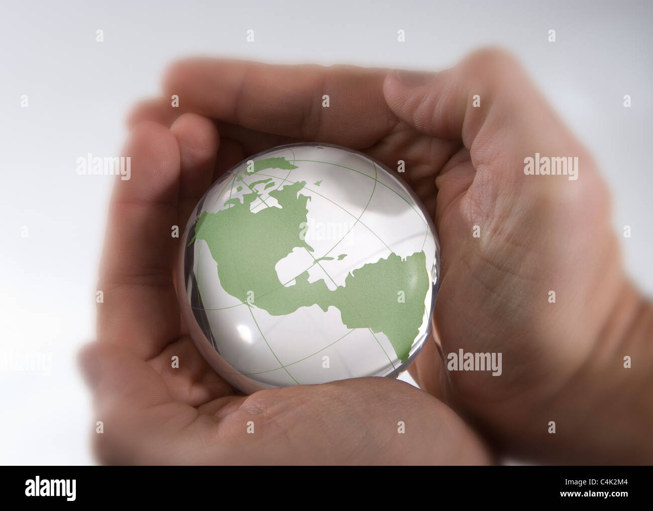 A man cradles a glass model of the earth in his hands. - Stock Image