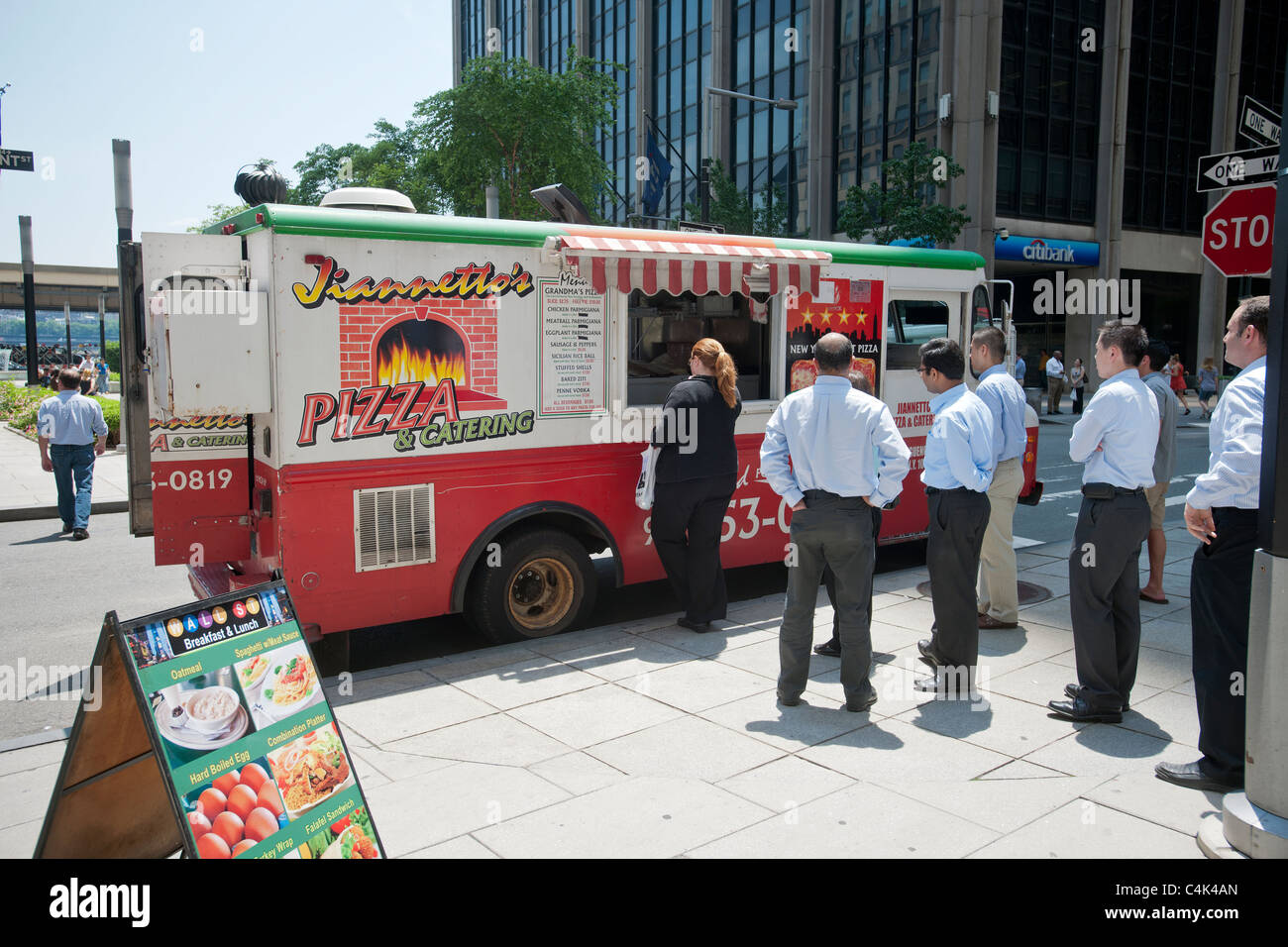 Customers line up for the popular Jiannetto's Pizza and Catering food truck in Lower Manhattan in New York - Stock Image
