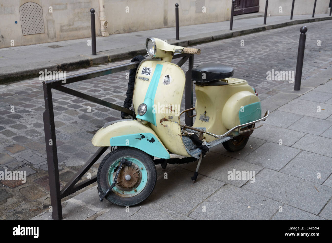 A rather battered Vespa scooter secured to a rail in the Rue Tournefort in the Latin Quarter, Paris, France. - Stock Image