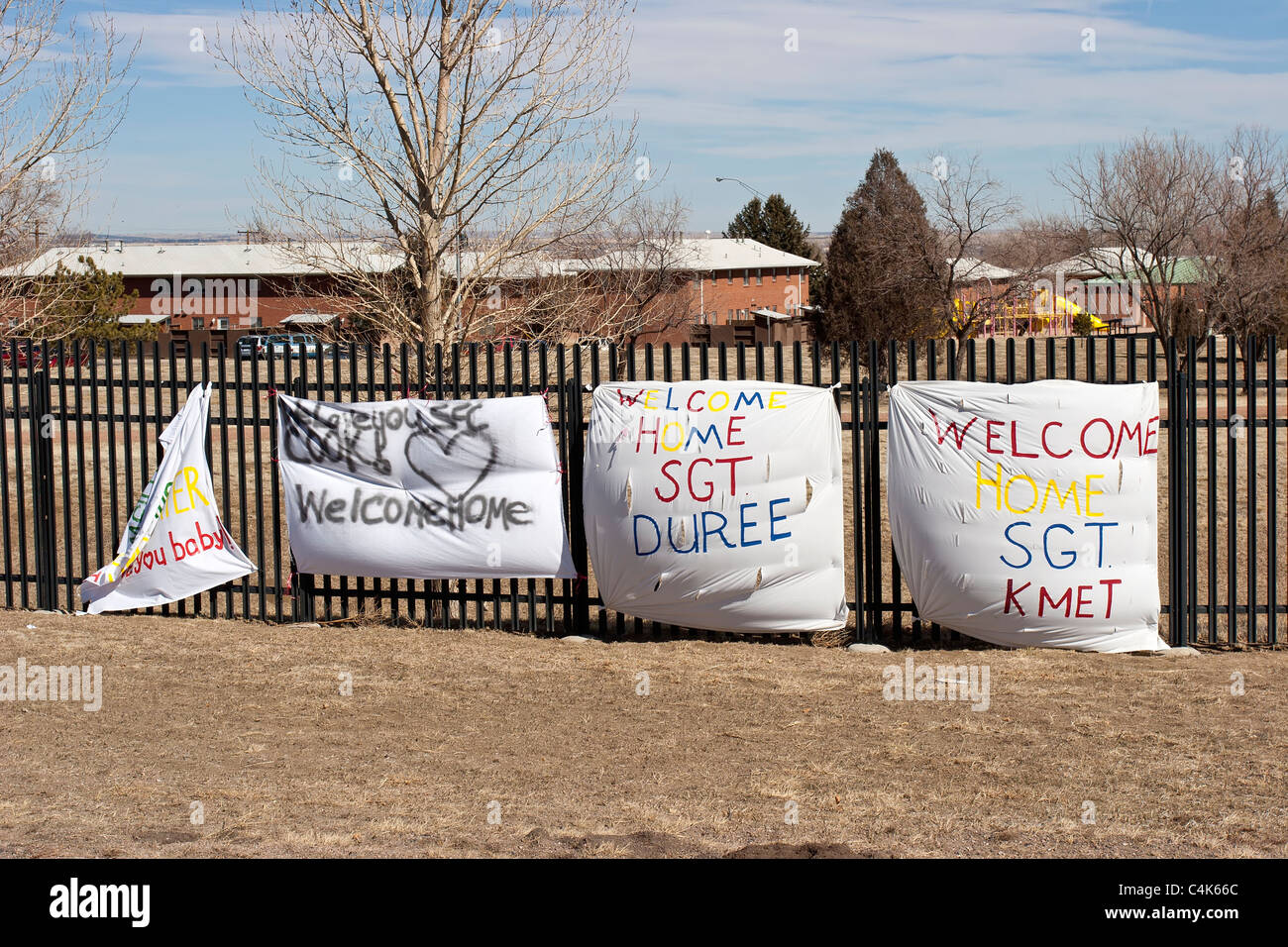 Fort Carson, CO - Sheets with welcome home messages drape a fence at the entrance of the Fort Carson army base. - Stock Image