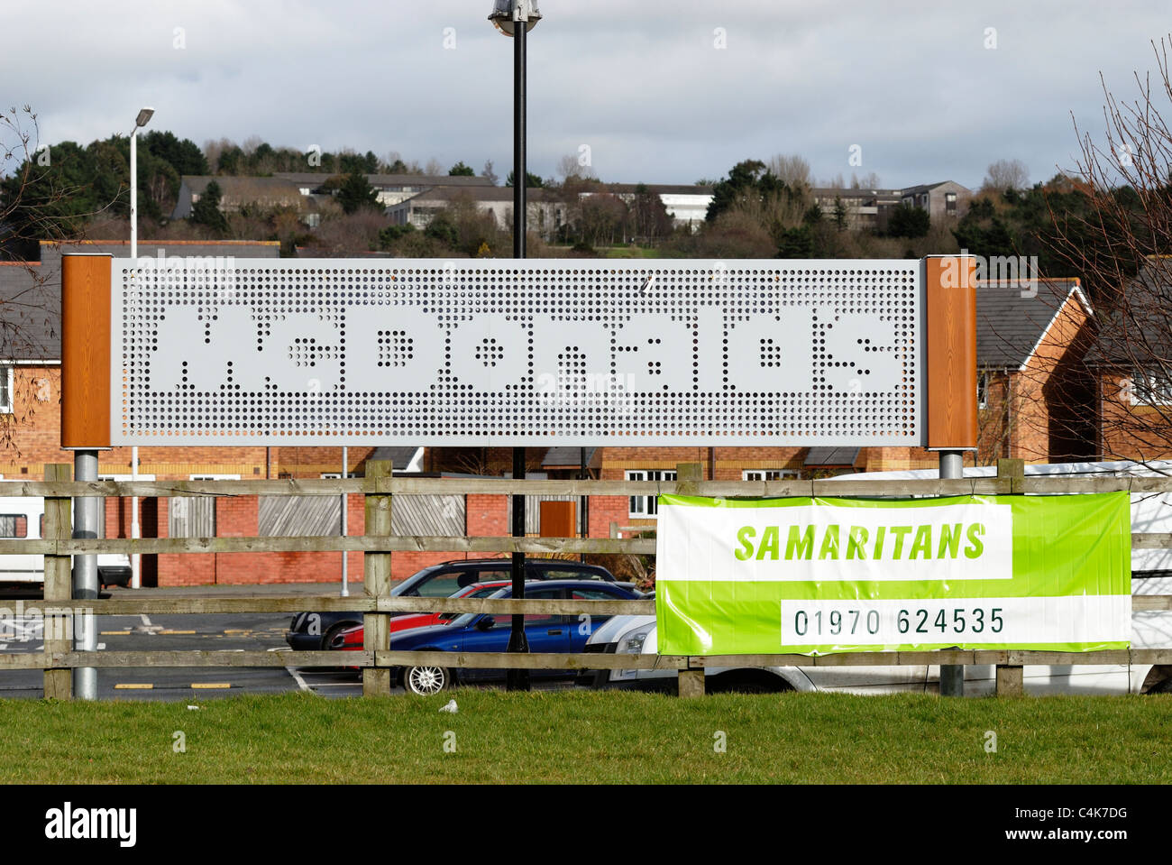 Signs for McDonalds fast food restaurant and the Samaritans helpline adjacent, Aberystwyth, Wales Stock Photo