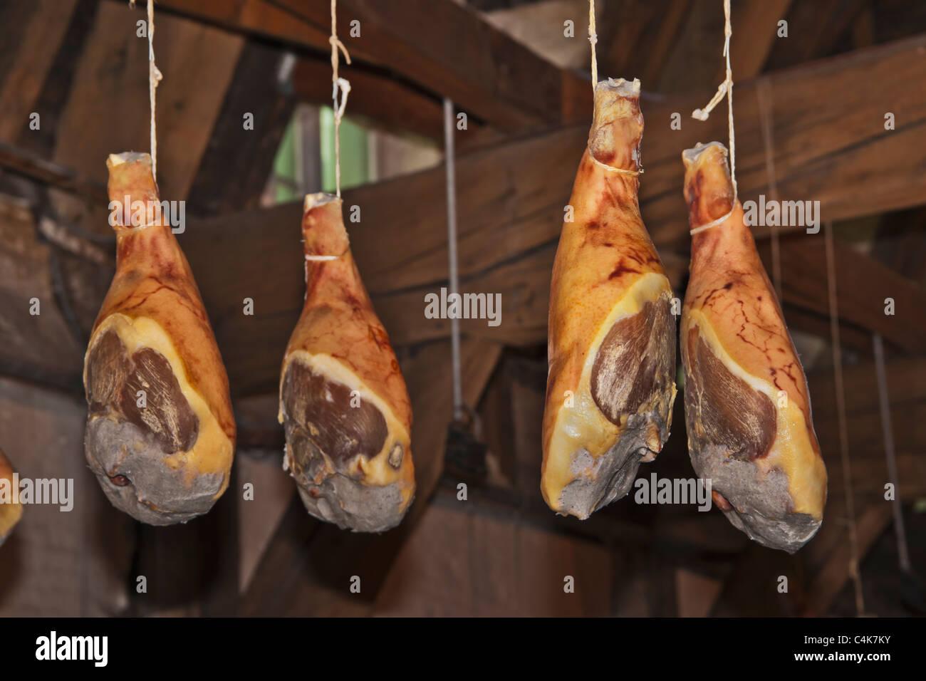 Räucherschinken hängen an der Decke einer Räucherei | Smoked ham hanging from the ceiling of a smokehouse Stock Photo