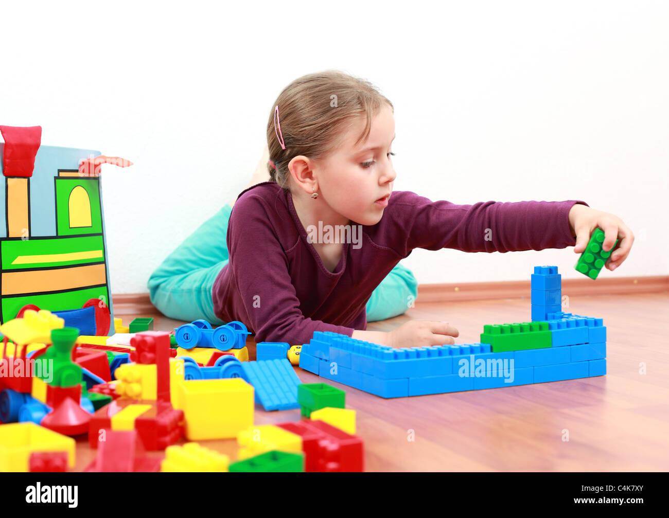 Adorable girl playing with blocks - Stock Image