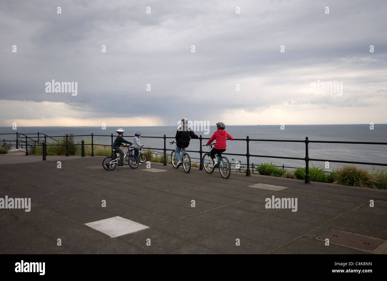 Family on cycles wearing safety helmets watching storm clouds over sea at Saltburn, Cleveland, UK - Stock Image
