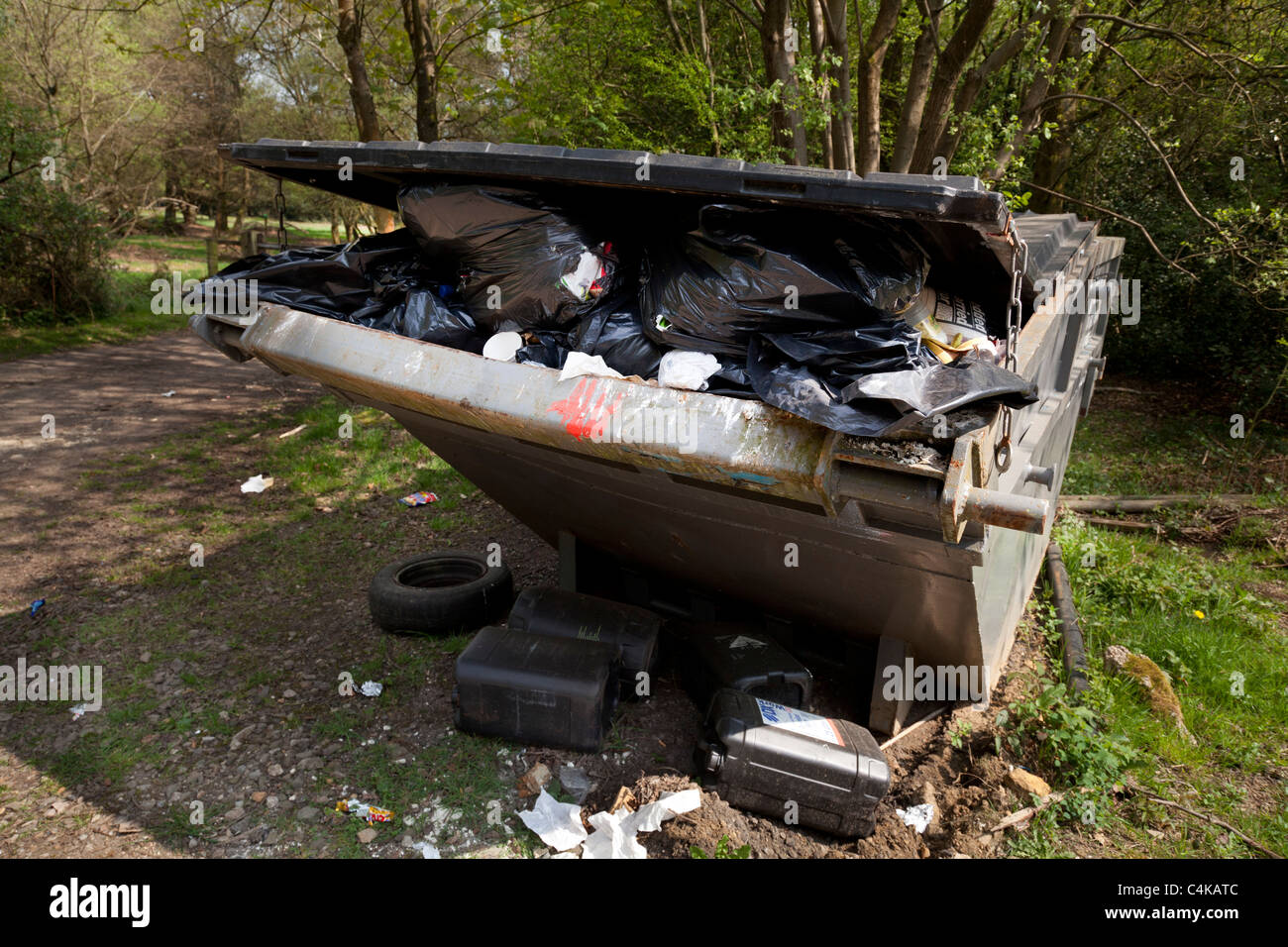 over full rubbish skip in countryside location - Stock Image