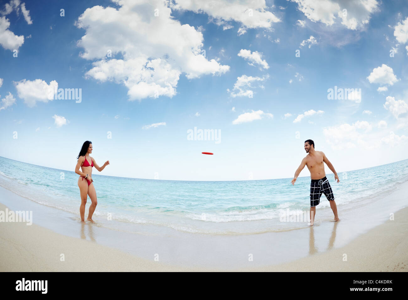 boyfriend and girlfriend playing with frisby on tropical beach. Horizontal shape, full length, fisheye - Stock Image