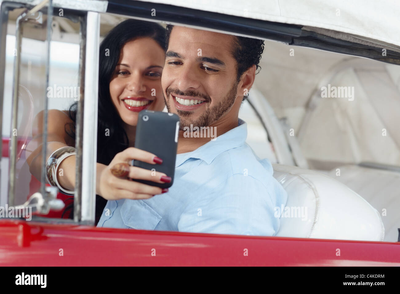 happy young man and woman smiling while taking snapshot with cell phone camera from red vintage convertible car - Stock Image