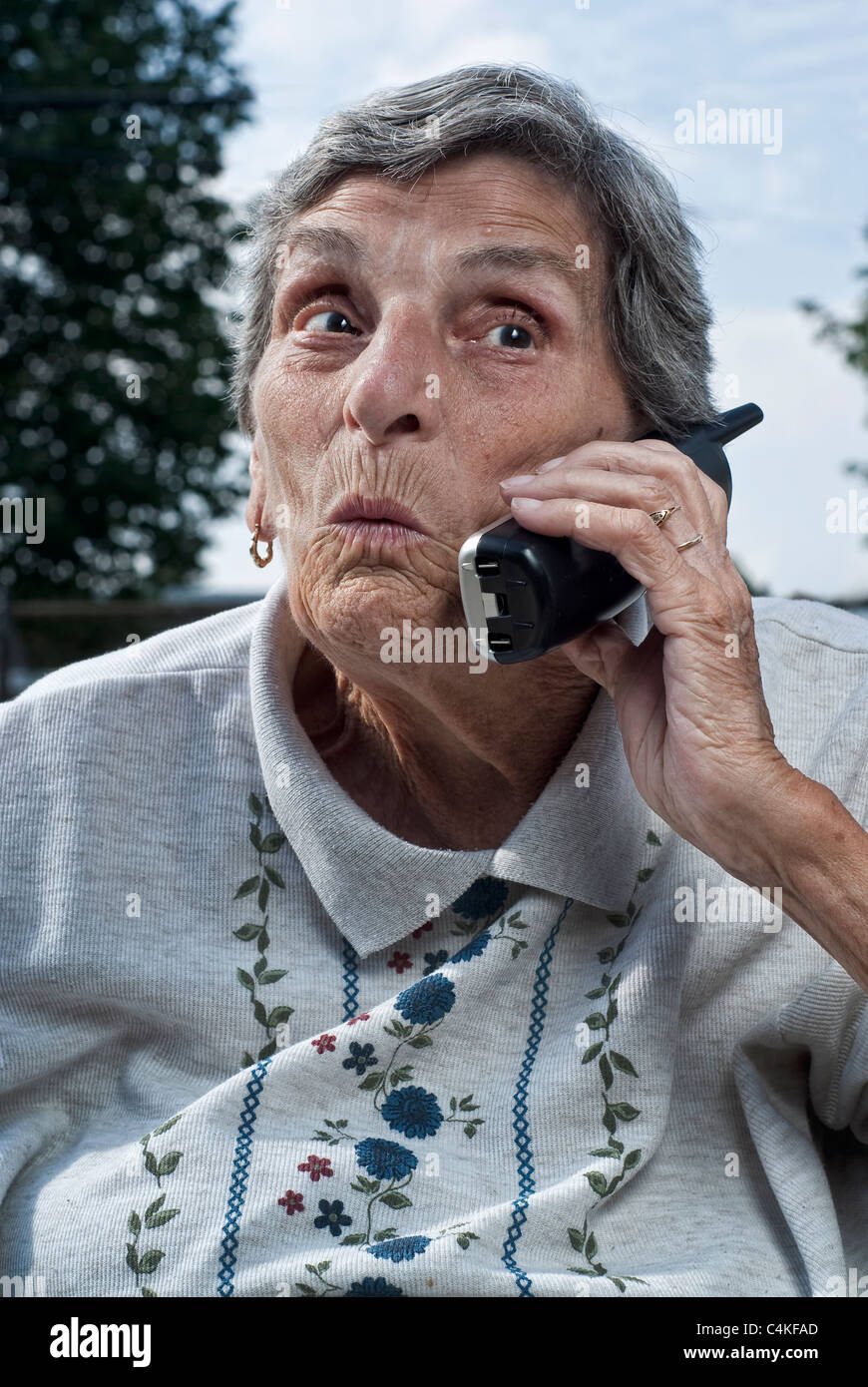 An elderly woman, with a look of surprise on her face, talks on a cordless phone. - Stock Image