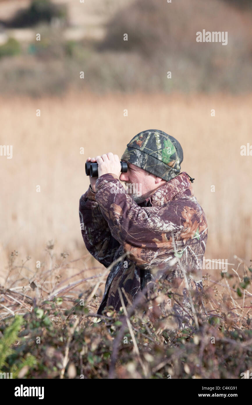Adrian Langdon bird watching; showing fieldcraft; Cornwall - Stock Image