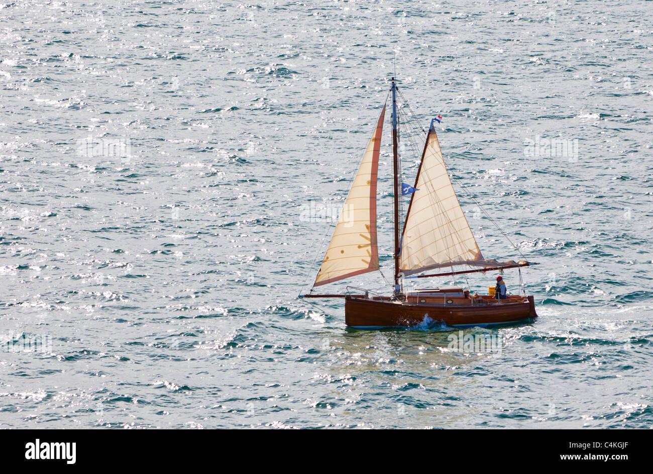 Small wooden sailing yacht at sea France Europe - Stock Image