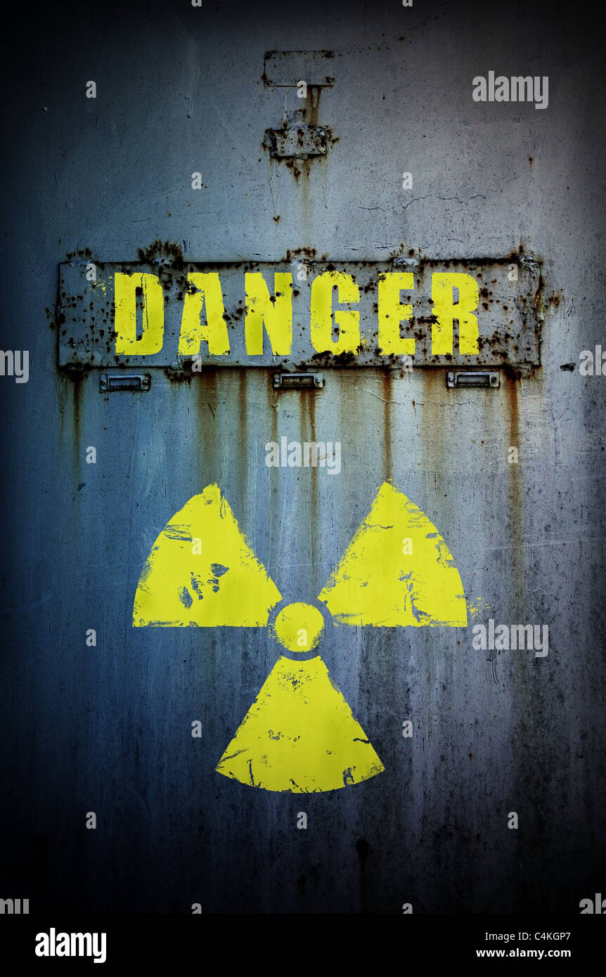 Part of old rusty door with radiation sign and 'danger' word. Radiation contaminated area. - Stock Image