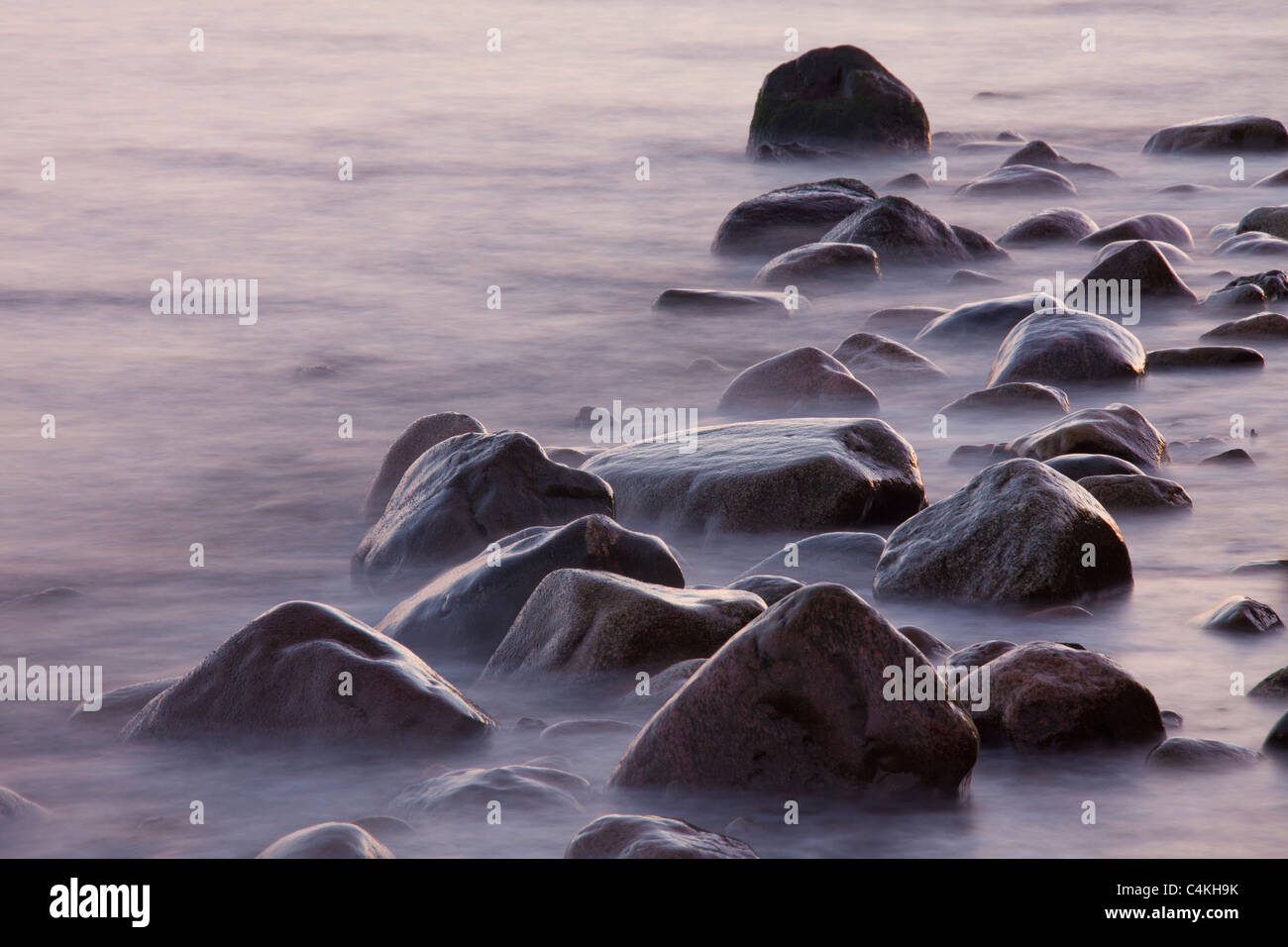Rocks and pebbles on beach in the surf at low tide, Germany - Stock Image