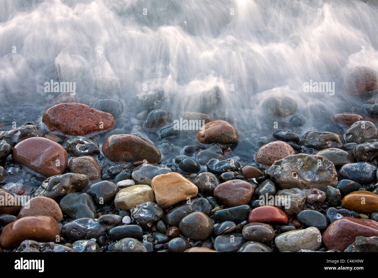 Pebbles on beach in the surf at low tide, Germany - Stock Image