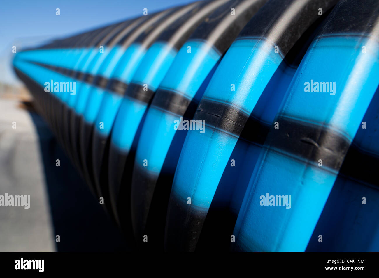 Blue and black stripes on grooved PVC water pipe surface - Stock Image
