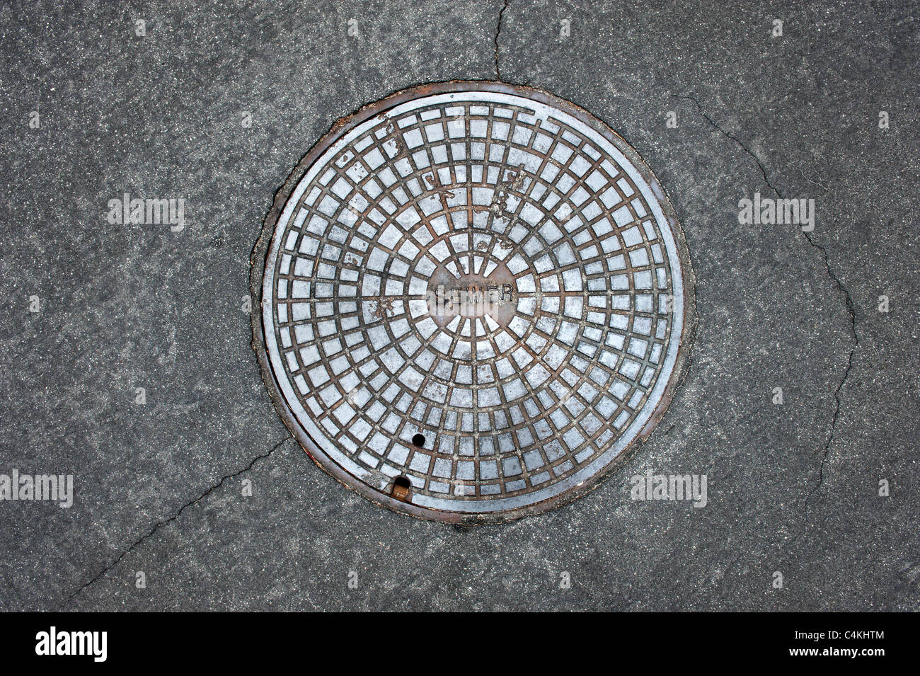 An old sewer manhole cover surrounded by an asphalt street - Stock Image