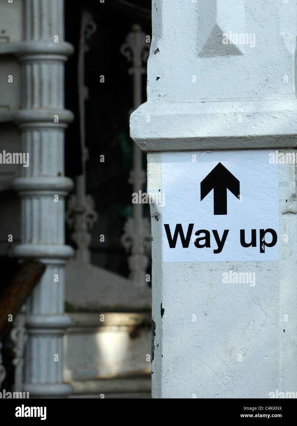 A way up sign points upwards by a metal spiral staircase. - Stock Image