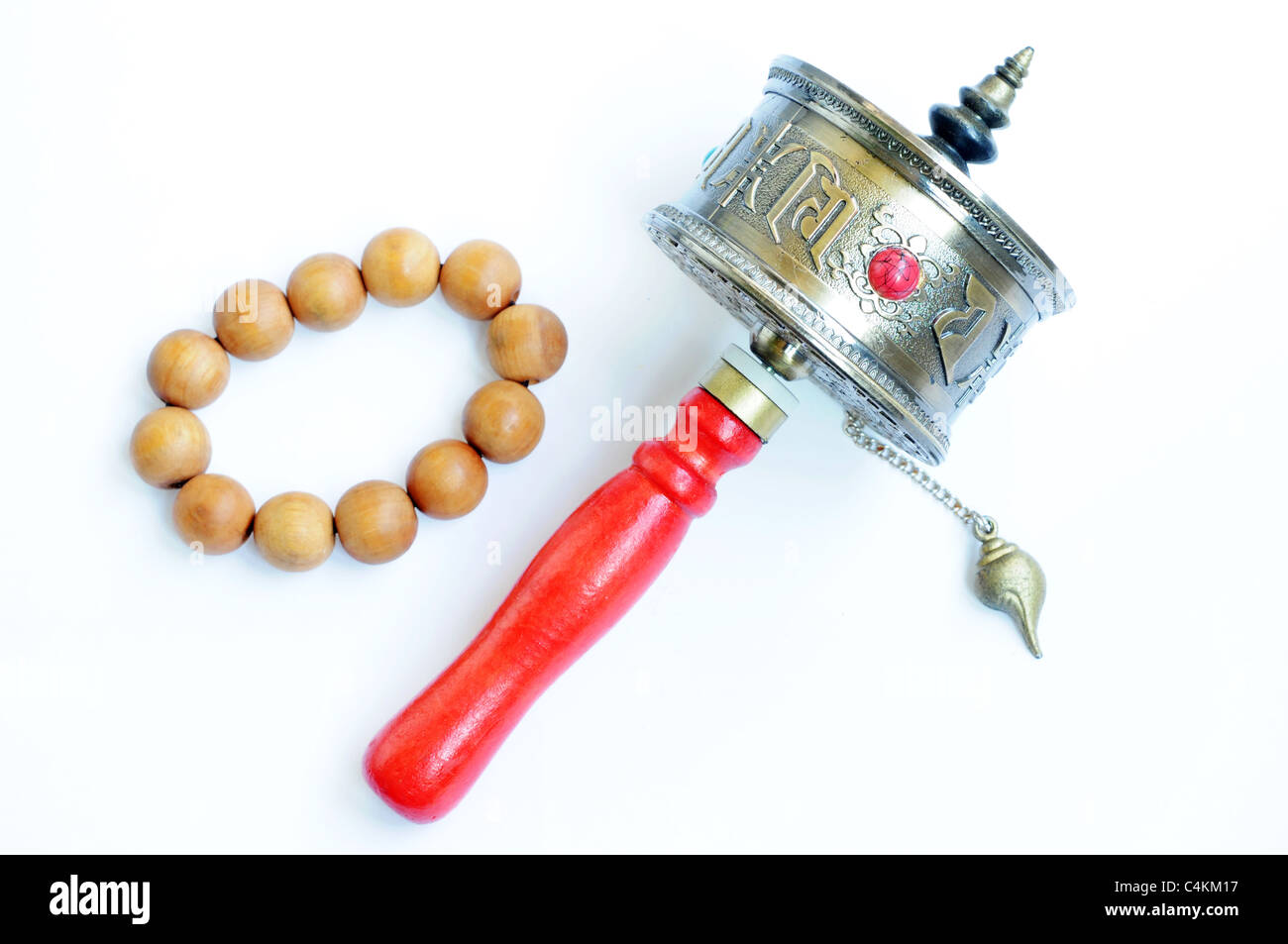 Closeup view of a Tibetan prayer wheel isolated on a white background. - Stock Image