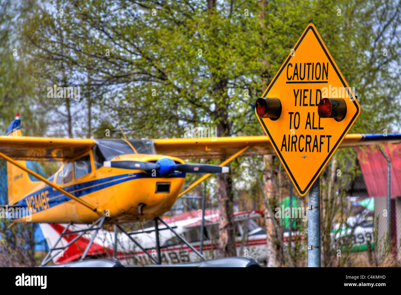 Float Plane and 'Caution Yield To All Aircraft' sign at Lake Hood in Anchorage, Southcentral Alaska, Spring, - Stock Image