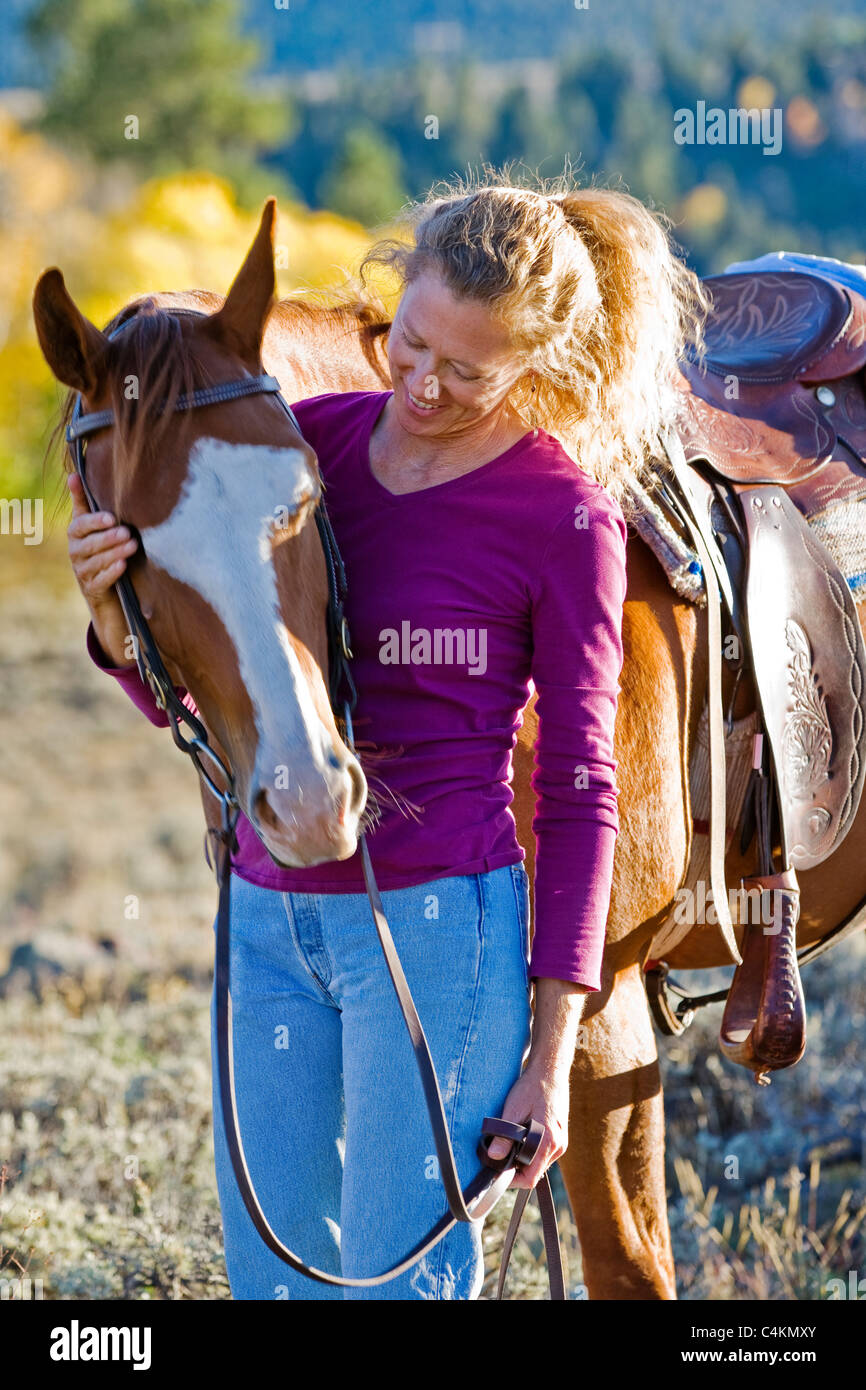 Portrait of a woman with her quarter horse in Colorado. - Stock Image