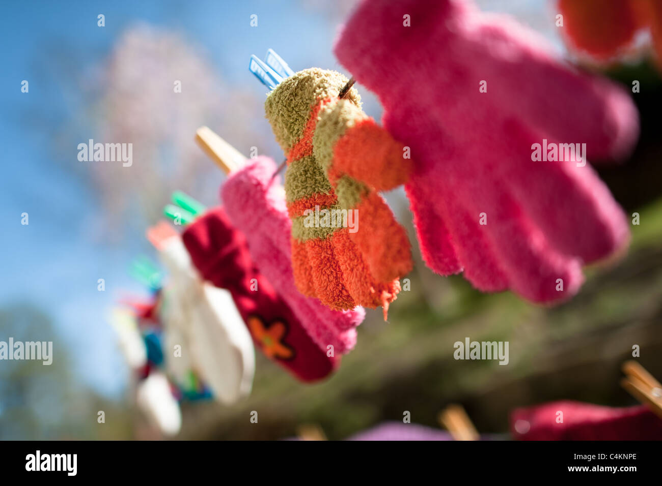 Colorful kid gloves hanging on a clothes line in the backyard of an apartment house, Czech Republic. - Stock Image