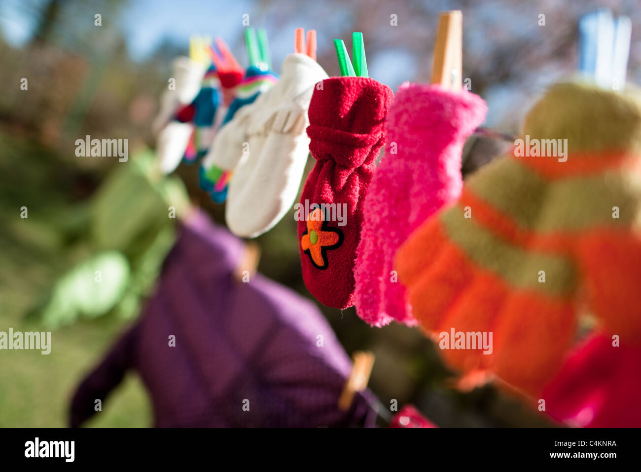 Colorful kid gloves hanging on a washing line in the backyard of an apartment house, Czech Republic. - Stock Image