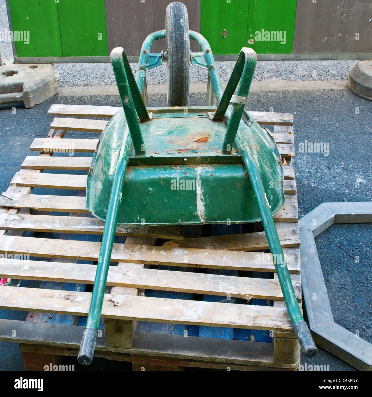 A workman's wheel-barrow on a pallet - Stock Image